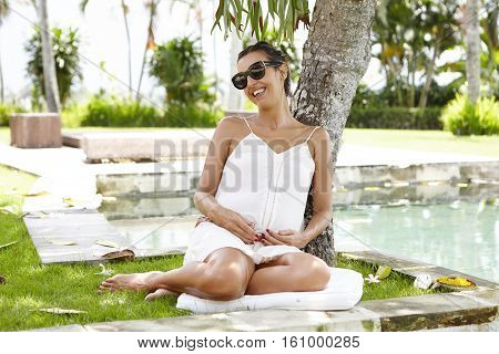 Young Expectant Mother In Shades Having Rest Under Tree During Nice Walk In Hotel Garden On Sunny Da