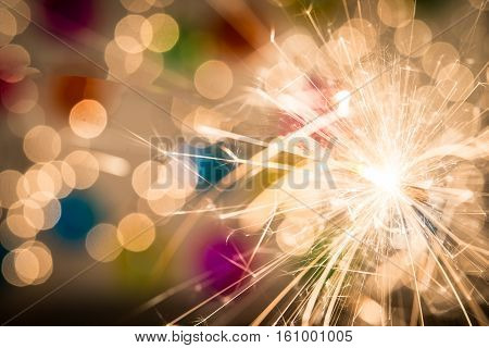 Christmas sparkler on colorful lights background and spase for text
