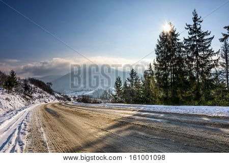 Snowy Road Through Spruce Forest In Mountains