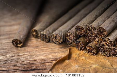 Cigarillo on wooden background close up with tobacco leaf selective focus