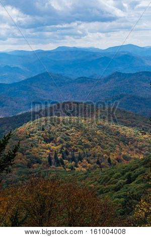 Light Highlights a Lower Mountain Covered in Fall Colors with ridge of mountains behind