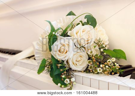 Bouquet of white roses lying on the keys of the white grand piano