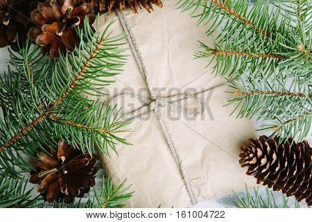 Gift wrapped craft paper with pine cones and fir branches top view
