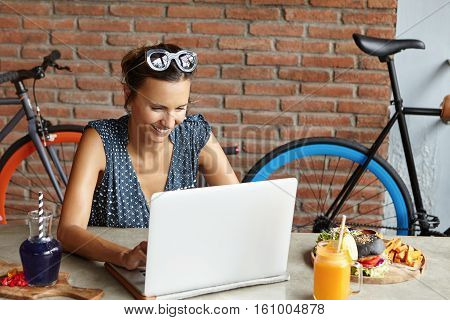 Stylish Female Wearing Sunglasses On Her Head Making Video Call To Her Boyfriend Using Free Wi-fi On