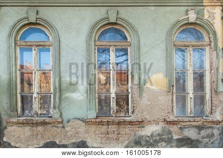 three dilapidated windows on the old hobbled home