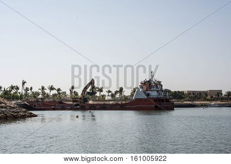 Boat dredger creating land coastline in Souly Bay Salalah Oman