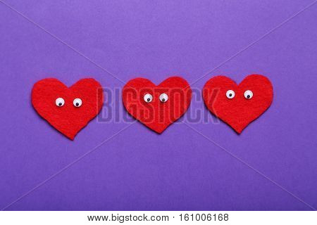 Red Hearts With Googly Eyes On A Purple Background