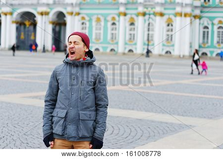 Young Man In Cap And Jacket Standing On The Palace Square And Yawns, Closing His Eyes.