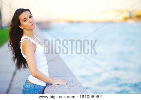 Portrait Of A Beautiful Slender Long-haired Brunette Girl In Jeans And A T-shirt On St. Petersburg's
