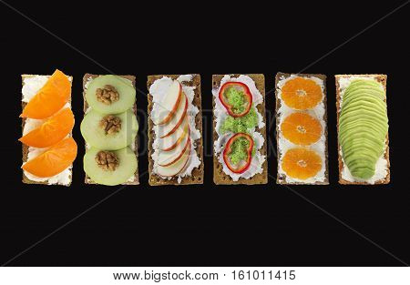 Sandwiches with cream cheese and fresh fruits and vegetables. Fresh healthy appetizer snack with crispbread on black background.