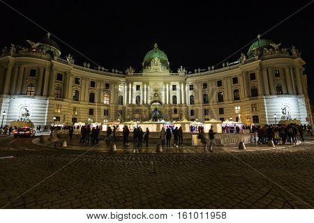 VIENNA AUSTRIA - 2ND DECEMBER 2016: The outside of the Hofburg Palace from Michaelerplatz in Vienna at night. Christmas Market Stalls and large amounts of people can be seen outside
