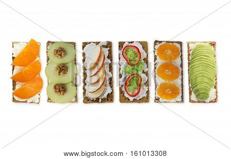 Sandwiches with cream cheese and fresh berries fruits and vegetables. Fresh healthy appetizer snack with crispbread on white background.