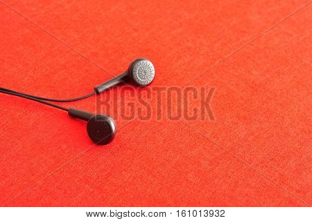 A set of earphones isolated against a red background