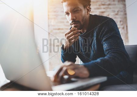 Young African man using laptop while sitting at his modern coworking place.Concept of business people full concentration.Blurred background, flares