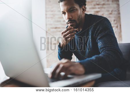 Young African man using laptop while sitting at his modern coworking place.Concept of business people full concentration.Brick wall on blurred background