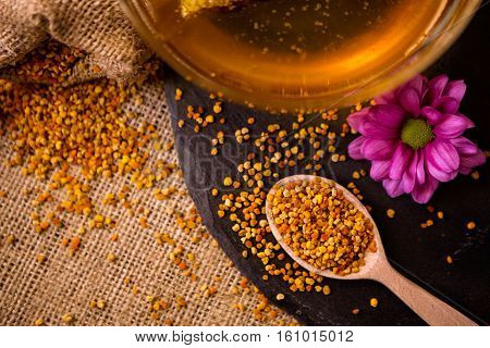 Bee pollen granules and propolis in wooden spoon and honey
