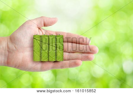 Batteries AA size in hand on green background
