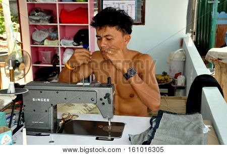 Hua Hin Thailand - January 1 2010: Barechested tailor using a Singer Sewing machine threads a needle at his roadside shop
