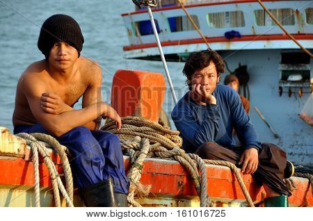Hua Hin Thailand - December 31 2009: Two Thai fishermen sitting on their boat while docked at the Hua Hin fishing pier following a day at sea