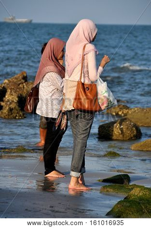Hua Hin Thailand - December 29 2009: Two Muslim women wearing traditional hajib head scarves wading in the warm ocean waters at Hua Hin beach