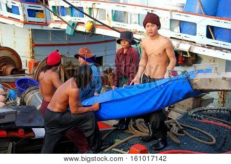 Hua Hin Thailand - December 30 2009: Crew members loading ice into the hold of their boat for the next day at sea while docked at the Hua Hin fishing pier *