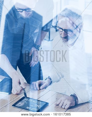 Double exposure concept.Team of business people making great work discussion in studio.Bearded man showing statistic repot, graph and diagramm on tablet.Skyscraper office building blurred background