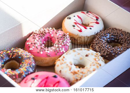 Colorful tasty glazed delicious doughnuts in the box