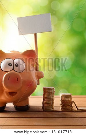 Piggy Bank With Blank Billboard On Table And Nature Vertical