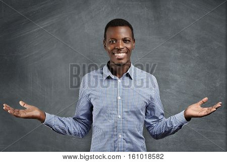 Successful African Businessman With Happy And Confident Smile Dressed In Blue Checkered Shirt Holdin