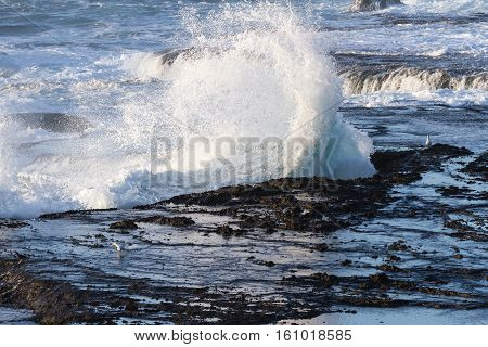 Waves Crashing On The Lava Rock Bluffs