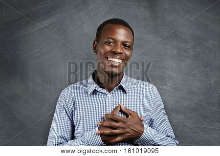 Touched And Grateful African Man Smiling Happily, Holding Hands On His Chest To Express His Gratitud