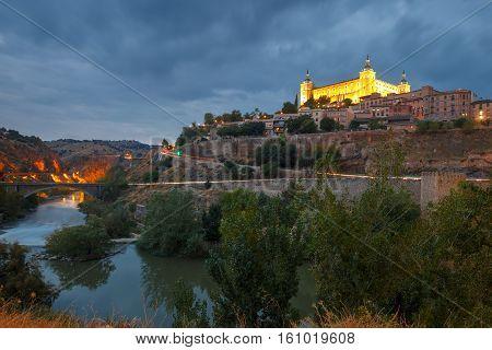 Old city of Toledo with Alcazar and river Tajo at night, Castilla La Mancha, Spain