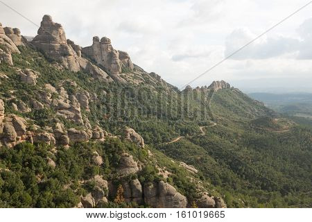 A track leads through trees under a rock tower ridge on the Mont Serrat complex Catalonia Spain Europe.