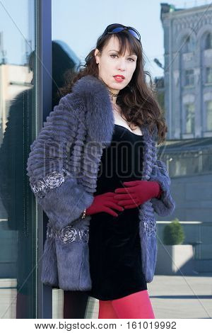 Sexy woman in a black dress red tights vinous gloves and a fur coat