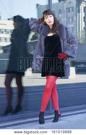 Sexy woman in a black dress red tights and a gray fur coat