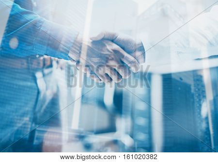 Double exposure concept.Close up view of business partnership handshake concept.Photo two businessman handshaking process.Skyscraper office building on the blurred background.Horizontal, flares