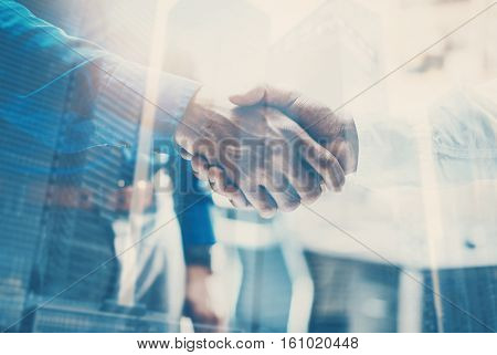 Double exposure concept.Close up view of business partnership handshake concept.Photo two businessman handshaking process.Skyscraper office building on the blurred background.Horizontal, flares effect
