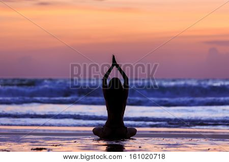 Silhouette Young Woman Doing Yoga On The Beach At Sunset