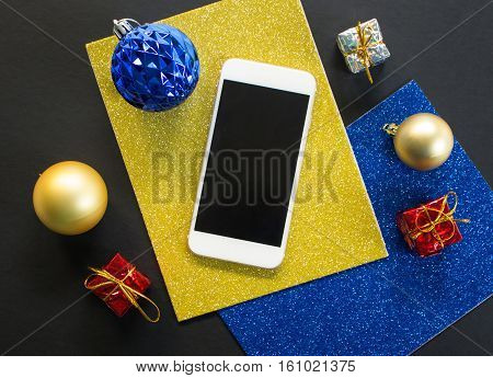 Christmas tree ornament and smartphone flat composition. White smartphone with black screen on table. Christmas or New Year mockup with personal gadget. Smartphone top view with winter holiday decor