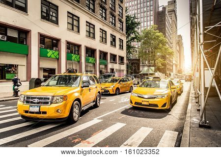 Several yellow cabs driving on New York's streets