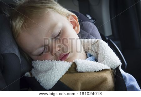 horizontal close up image of a little caucasian female toddler sound asleep in her carseat in the car.