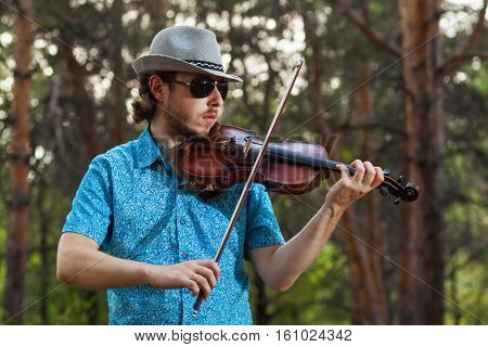 Professional musician playing the violin in the forest