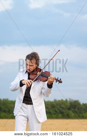 Violinist playing the violin in the field