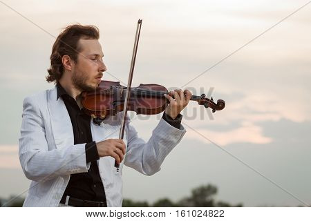 Professional violinist in profile outdoors close up horizontal