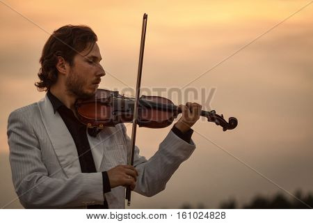 Professional violinist with the violin late evening silhouette