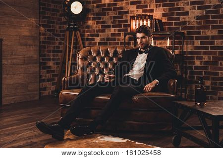 Young Man In Suit Resting On Sofa With Glass Of Brendy After Working Day