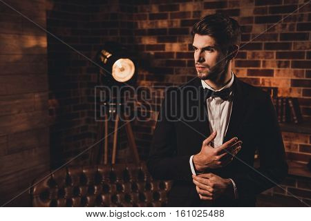 Handsome Sexy Man In Black Suit Fastening Buttons On The Sleeves