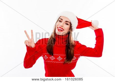 Cheerful Woman Holding Pompon Of Santa Hat And Gesturing V-sign