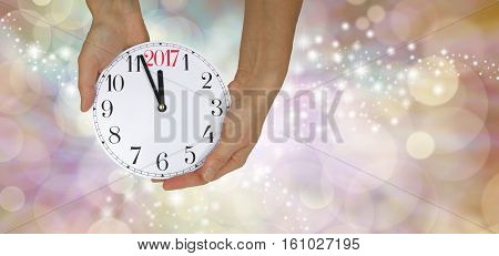 It's Nearly New Year 2017- Wide sparkling champagne colored bokeh background with a pair of hands holding a clock face showing three minutes to midnight on the left side and copy space on right