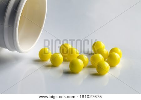 Prescription pill bottle spilling pills on to surface isolated on a white background. Vitamins spilling out. Healthcare traditional medicine and flu concept - drugs.